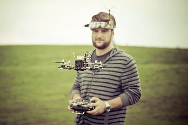drone racer with FPV racing goggles hovering