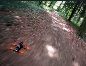 racing drone flying in the woods blurred